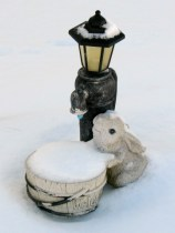 water fountain covered in snow, looks like a bunny with a bucket.