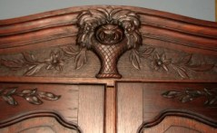carved basket of flowers and vines carved into wooden armoire