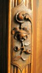 macro photo of carved wooden flower and stem on armoire