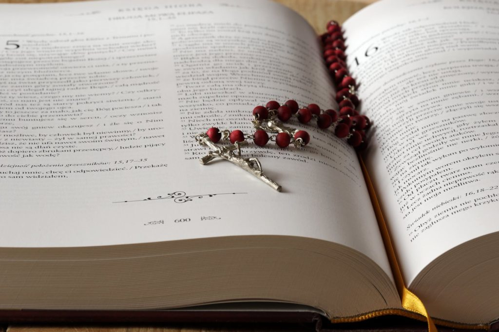 Rosary beads on a Bible Catholic church settlements Merson Law PLLC