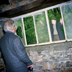 Inside the Merz Barn, viewing the site (and Fred Brookes) through the rotting windows
