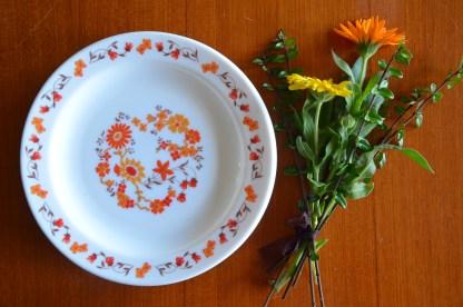 Assiette à dessert de la marque Arcopal, collection Marguerite et Tournesol, motif grandes fleurs oranges.