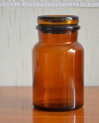 Petit pot d'apothicaire en verre ambré avec un bouchon plat