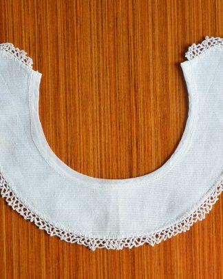 Joli col rond blanc à coudre sur un vêtement.
