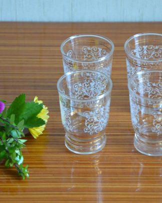 Lot de 4 verres à liqueur en verre avec des motifs d'arabesque et deux liserés en or.