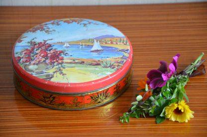 Boite ronde vintage en métal. Motif de bateau dans un port et rosier en premier plan.