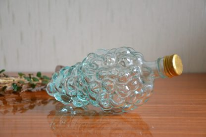 Bouteille en verre en forme de grappe de raison, se ferme avec un bouchon en métal. Se pose sur le côté.