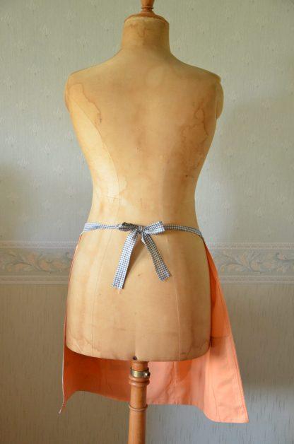 Tablier orange avec 3 poches motif bleu et locomotive. En tissu, tablier vintage qui s'accroche avec un noeud.