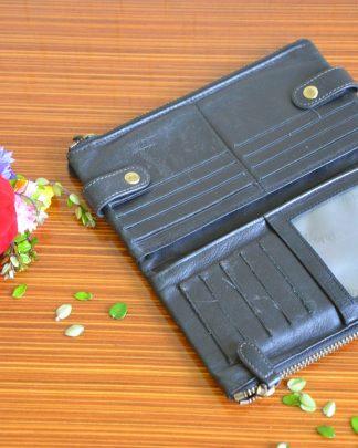 Pochette en véritable cuir noir de la marque Katana. Possède différents emplacements pour les cartes bancaires, de fidélités . Porte-monnaie se fermant avec une fermeture éclair, la pochette se referme pas des boutons pressions.