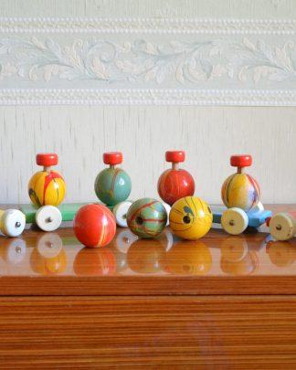 Petit train en bois avec des boules en bois qui se retirent. La peinture est comme laquée. Les wagons s'attachent les uns aux autres grâce à des attaches en métal. J'ai trouvé ce jouet dans le grenier d'un vieux monsieur, le jouet doit bien avoir 50 ans. Il y a 1 locomotive, 3 wagons et 7 boules. Un wagon fait 16 cm de long et 5.5 cm de large (sans les roues). La locomotive fait 9 cm de haut. Les boules font environ 5.5 cm de diamètre. Un wagon avec les boules fait environ 10 cm de haut. Le tout fait 1.002kg. .Les wagons sont d'une couleurs unis et les boules sont multicolores.