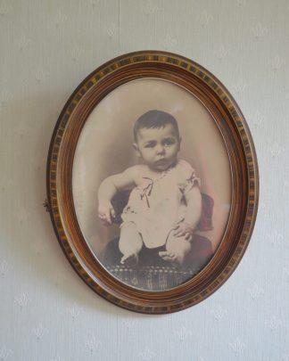 Cadre ancien ovale en bois avec une photo de bébé en noir et blanc. Cadre de 47.5 cm de haut et 37.5 cm de large.