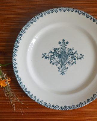 Plat de service plat Alhambra, Salins. Vers 1880. Plat en faïence blanche à monochrome central floral et bordure sur le marli. Au centre, médaillon en bouquet de fleurs et en rinceaux vert-bleu; sur le marli, guirlande de fleurs de même couleur