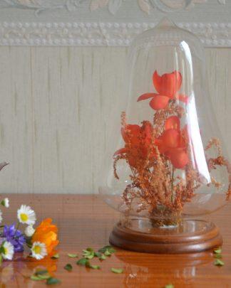 Globe en verre, support en bois, fleurs en plastique et tiges naturels.