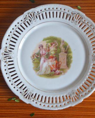 Assiette en porcelaine vintage, manufacture schwarzenhammer bavaria, motif de 3 femmes en toge devant une statue. Le marli est ajouré.