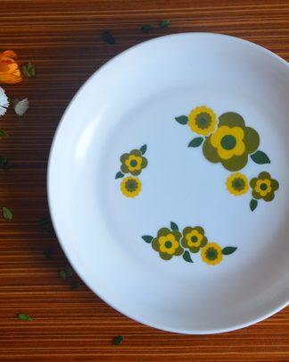 Assiette en opaline de la marque Arcopal France, motif des année 70 fleurs jaune et verte