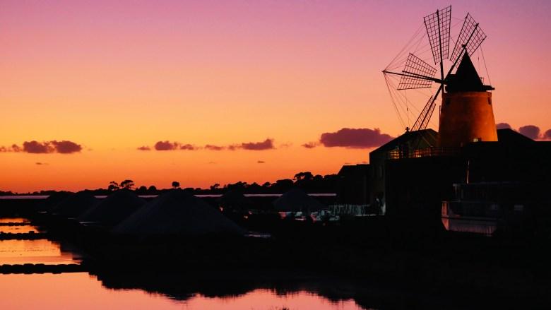 Un coucher de soleil absolument magique sur les marais salants et moulins de la Riserva Naturale dello Stagnone, depuis le restaurant Mammacaura à Marsala.