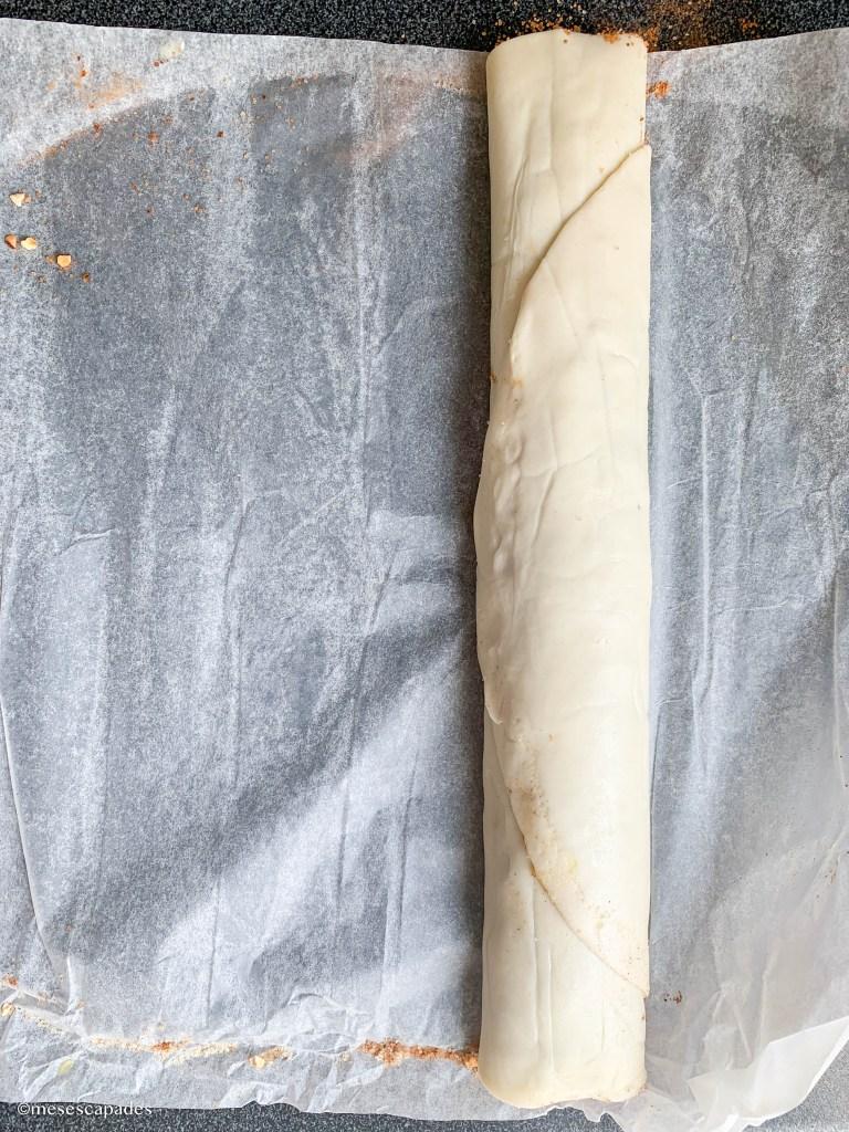 Rouler la pâte couverte de cannelle pour les cinnamon rolls, une étape essentielle des cinnamon rolls
