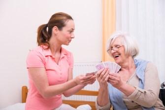 Pflegerin spielt Karten mit Seniorin
