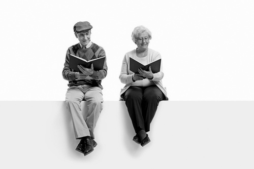 Seniors seated on a panel reading books