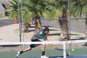 Bulldog Tyler Hughes goes down to return a Pirate's serve Tuesday on the hill. Hughes went 2-1 in his matches. Photo by Lou Martin