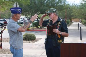 Veteran and Mayor Al Litman salutes and presents fellow veteran Pete Blair a plaque honoring Blair as the 2014 Veterans Day parade Grand Marshall. Photo by Lou Martin