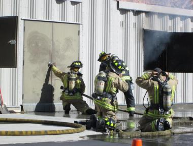 Once enough personnel was on scene, they prepare to enter the burning structure, feeling the door for heat before proceeding. Photo by Stephanie Frehner.