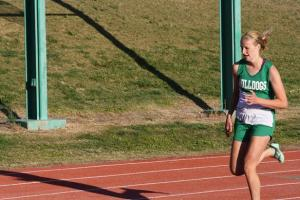 Lady Dawg Emma Dodenbier makes the turn on her way to a first place finish in the 400 meter dash. Photo by Lou Martin