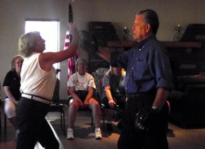 Peggy Pope and John Hughes demonstrate an upper strike using the palm of the hand. A strike such as this can be effective to use toward the chin or the nose of an attacker at a previous self-defense class. Photo by Teri Nehrenz.