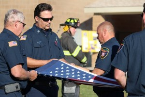 Mesquite Fire Capt. William Martinez cuts the stripes of the flag to prepare it for burning during the flag retirement ceremony held at the closing of the 1000 Flags over Mesquite. Photo by Teri Nehrenz