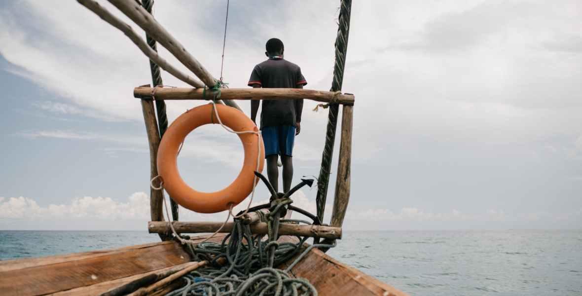 unrecognizable man on sailboat in sea