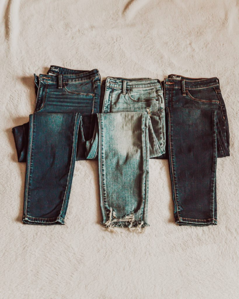 Three pairs of affordable denim jeans on white rug.