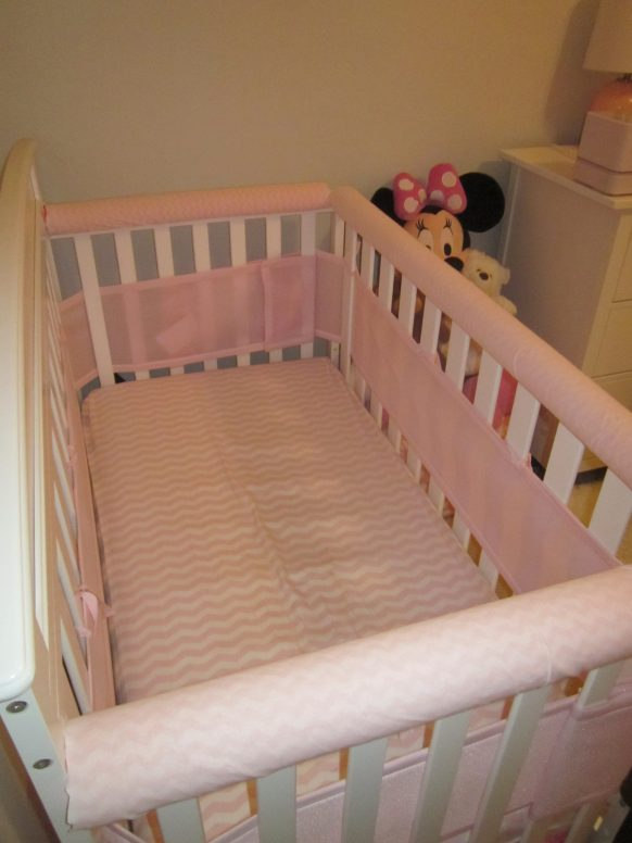 Crib with fabric-covered pool noodles over the railings