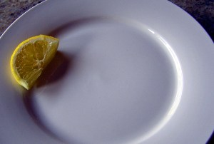 Empty plate with lemon wedge