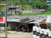 Sur le chemin de Sangarkot, maisons au toit de bric à brac