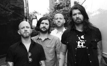 Taking Back Sunday band photo, black and white. The band appear to be standing between two buses and look a bit miserable. Cheer up lads!