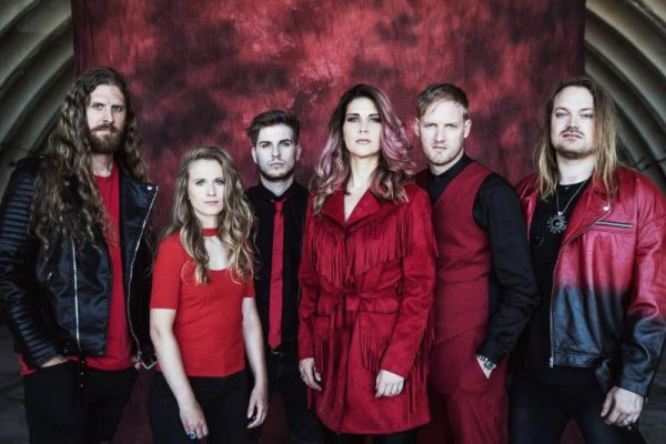 Delain band members, dressed in red and black stood, red backdrop.