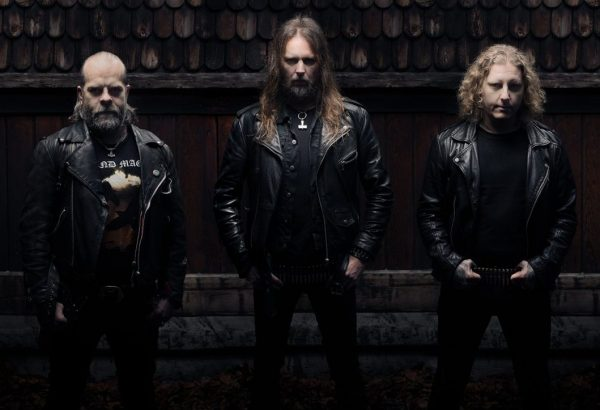 Grand Magus 2019 band photo of them in front of what appears to be a wooden shack. All three members are wearing black jeans, t-shirts and leather jackets with bullet belts.