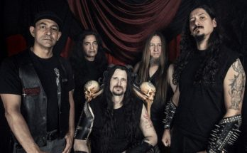 Possessed band colour photo. 4 members of the band are standing in front of a dark red hanging cloth backdrop. They are all wearing black, three of them with long hair, the furthest right has large studded leather bracers which cover his entire forearms. Singer Jeff Becerra sits in front with skulls on the back of his chair, one over each shoulder.