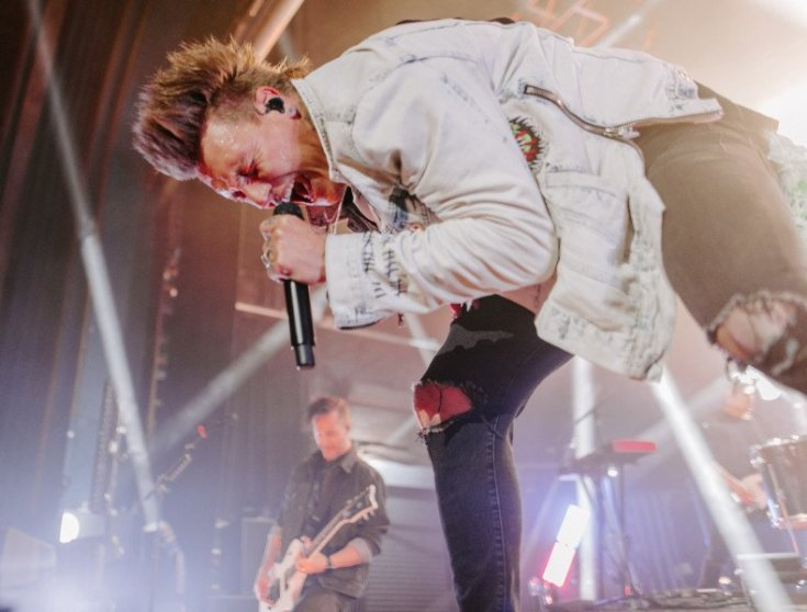 Papa Roach live photograph of Jacoby Shaddix screaming into the microphone doubled over.