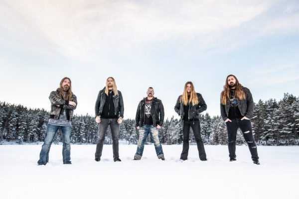 Sabaton band photo. The band are standing in an open field covered in snow. Around the edge of the field is a thick wall of trees which are also thick with snow.
