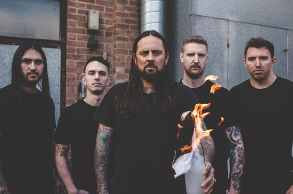 Thy Art is Murder Band Photo. The band are all dressed in black standing in frond of a building while their lead singer holds a molotov cocktail (a glass bottle filled with petrol with a burning rag pushed down the neck).