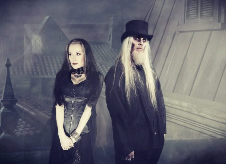 Bloody Hammers band photo. The band consists of two members, a man and a woman both in Victorian style gothic clothing. She has long black hair with white or pale strips at the front, she has narrow pointed eyebrows and dark red lipstick. She wears a black lace collar and a black leather corset over a velvet dress. He wears a top hat over his long bleached blonde hair. He has a long beard which matches the colour of his hair and light makeup that darkens his eyes and at the sides of his face to make him look dead. He wears a long black coat.