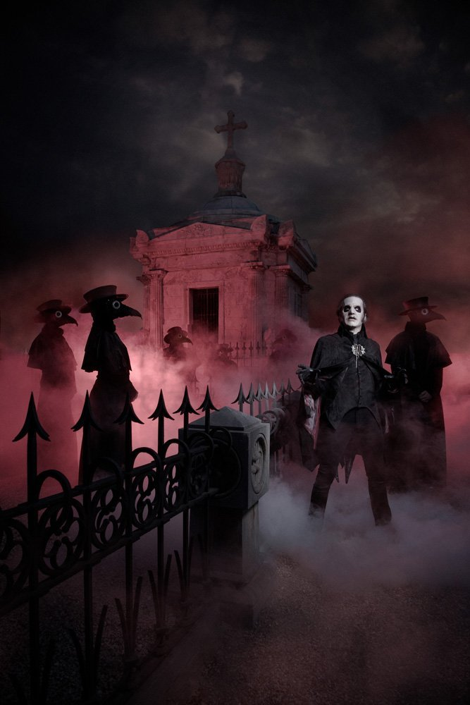 Colour image of Ghost. The band stand in a cemetery - spiked railings run diagonally from the front left corner to the right middle of the image, a large mausoleum stands at the back centre. There is mist all around and a dark red light illuminates the building. The Ghouls are all dressed in plague doctor outfits and stand side on, facing to the right. Cardinal copia stands facing straight ahead wearing his black velvet bat cloak.