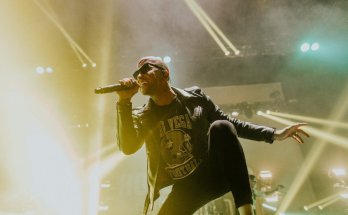 Danny Murillo of Hollywood Undead, colour photograph. Dylan has one foot up on the monitor while singing, he's wearing an American Football t-shirt under a leather jacket. and sunglasses. Behind him beams of light shine past him