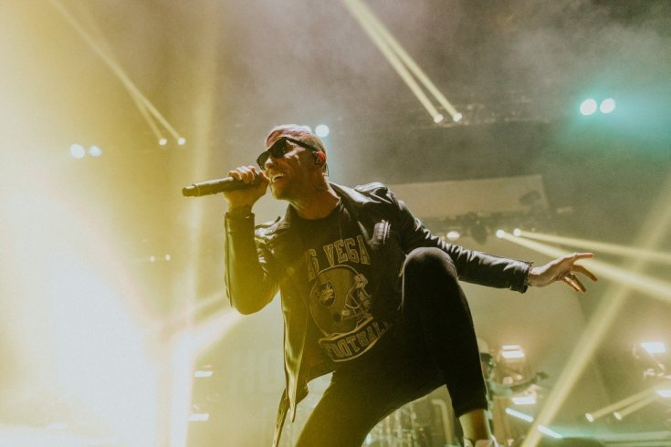Daniel Murillo of Hollywood Undead, colour photograph. Dylan has one foot up on the monitor while singing, he's wearing an American Football t-shirt under a leather jacket. and sunglasses. Behind him beams of light shine past him