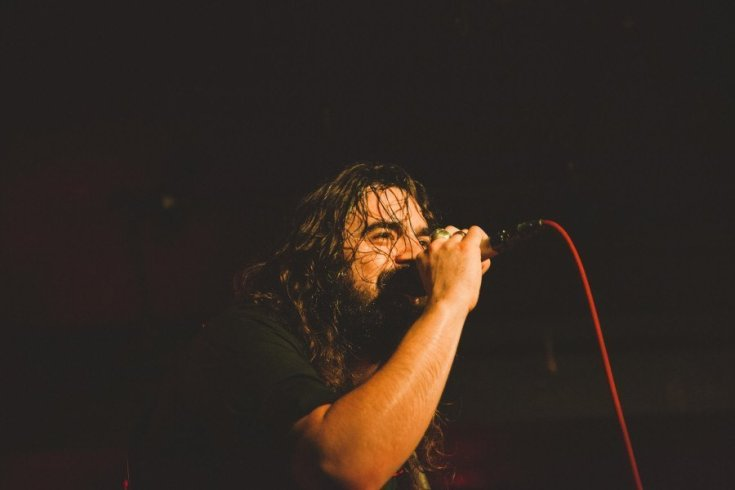Photo of FYNN CLAUS GRABKE of the picturebooks singing into a microphone. The photo is very dark, Fynn holds a microphone to his face and seems to be smiling under his thick beard. His hair is wet from sweat and stuck to his face, on his hand holding the microphone he has two large rings.
