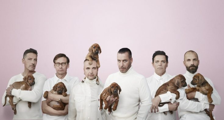 Rammstein band photo. The band are all wearing white and are stood in front of a pink background. Each holds a puppy apart from one member who has the puppy on his head.