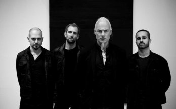 Black and white photo of the band Samael. All band members are dressed in black, wearing black jackets, standing against a white and black background.