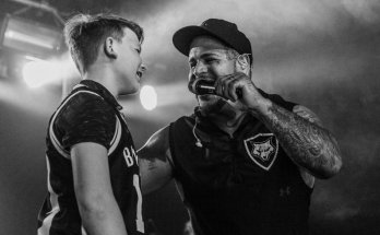Tommy Vext of Bad Wolves with a young fan singing Zombie black and white photo