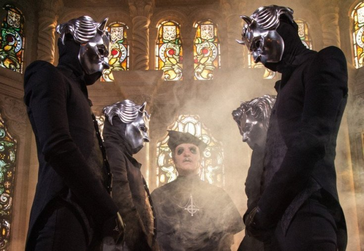 Ghost band photo. The band are standing in a crypt with stained glass windows behind them. Two Ghouls stand to the left, two to the right with the pairs facing each other. Between them through the smoke of incense is Cardinal Copia.